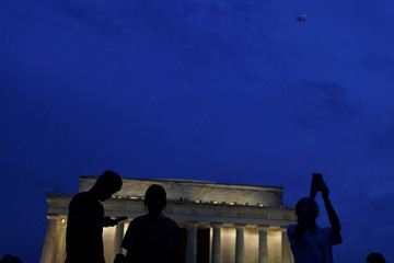 People take photos prior to a firework show during the 4th of July Independence Day celebrations at the National Mall in Washington