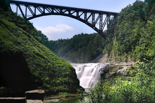 landscape photo of Upper waterfall in Letchworth State Park, State New York,USA. The bridge is over the waterfall.