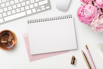 feminine workspace / desk with blank open notepad, keyboard, stylish office / writing supplies and pink peonies on a white background, top view Wall mural