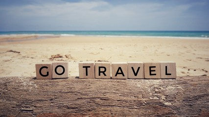 Motivational and inspirational quote  - 'Go Travel' written on wooden blocks. With blurred vintage styled background.