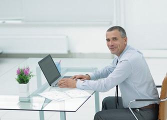 smiling businessman sitting at Desk and looking at camera