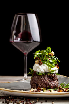 a large piece of juicy steak with egg poached and rucola salad with goat cheese in olive oil, lies on a plate. On the table is a glass of red wine. concept of a beautiful dish serving for a restaurant