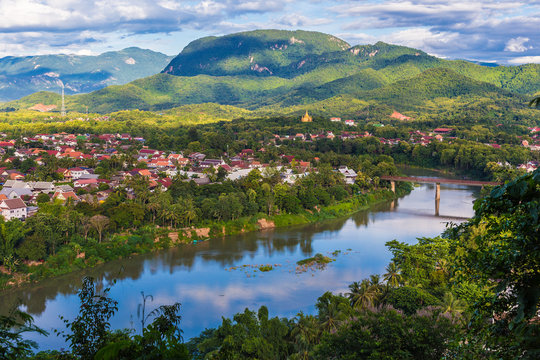 View of Luang Prabang and Nam Khan river in Laos with beautiful sunset light bathing the mountains