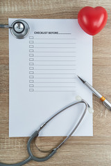 Stethoscope and pen with red heart on empty checklist form