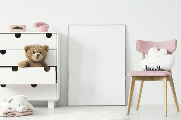 Empty poster with place for your picture standing on the floor in bright kid room interior with white cupboard and pink chair