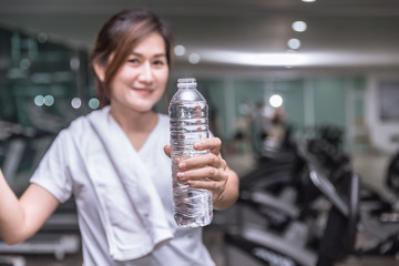 healthy asian woman hand hold show bottle of drink water with sport club background