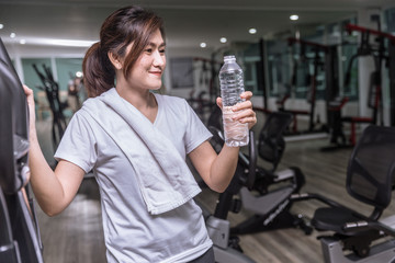 asian girl hand hold drinking water bottle in sport club fitness and smiling