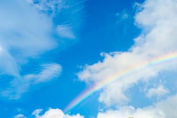 Rainbow on the blue cloudy sky