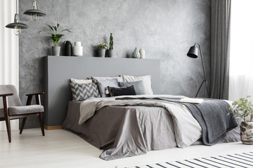 Stylish standing lamp next to a bed in a monochromatic grey bedroom interior with a footstool, an armchair and decorative plants in pots against the wall. Real photo.