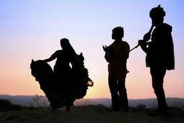 Woman dancing in front of setting sun with two musicians