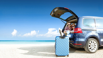 Summer trip on beach. Big blue car with two people. Free space for your text.