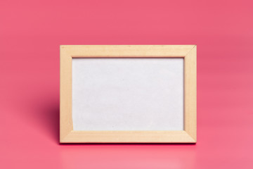 Blank photo frames on pink colored background