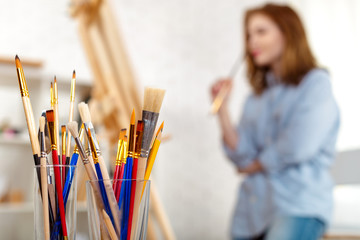 Painting supplies brushes and easel, workplace of artist.