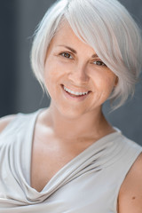Beautiful blond caucasian woman with stylish haircut looking cheerfully in the camera on a blurred blue background