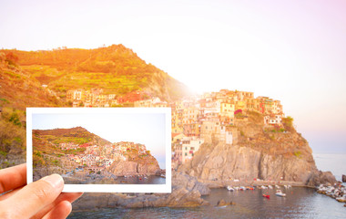 Hand holding Instant photo or photography in Europe at Village of Manarola, on the Cinque Terre coast of Italy with sunset, Concept holiday, tourist on vacation background, Italy landscape.