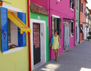 Smiling woman poses by the entrance of a colorful house by the Venetian canals.