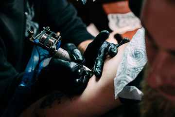 cropped shot of tattooing process of tattoo on shoulder in salon