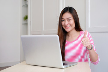 Young asian woman thumb up while working with laptop computer, people working with positive expression