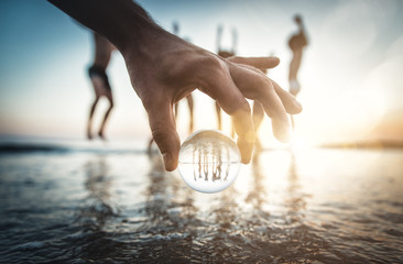 Artistic portrait of friends with reflection inside a glass sphere