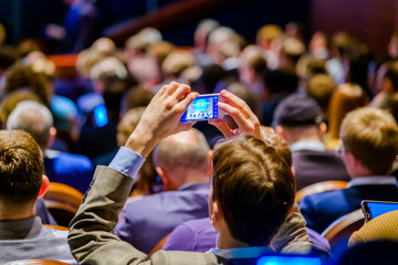 Man takes a picture of the presentation at the conference hall using smartphone