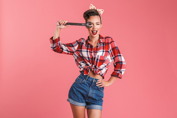 Amazing young pin-up woman holding wrench.