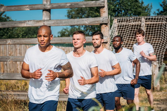 portrait of multicultural young soldiers running on range