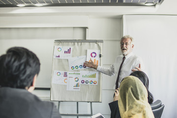 old manager man exploring and pointing to flip chart for young employee