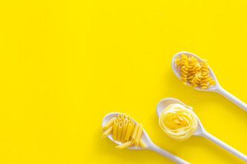 Different raw pasta. Fusilli, penne, fettuccine in spoons on yellow background top view copy space