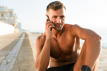 Handsome strong mature sportsman talking by mobile phone