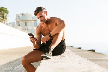 Mature sportsman chatting by mobile phone