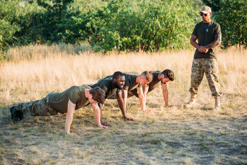 tactical instructor in sunglasses examining multicultural soldiers doing push ups on range