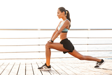Profile photo of energetic brunette sportswoman 20s in tracksuit doing lunges, and stretching legs on boardwalk at seaside