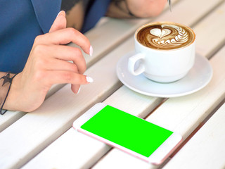 Mockup image of white mobile phone with blank black screen and hand holding hot latte coffee on vintage wood table in cafe.