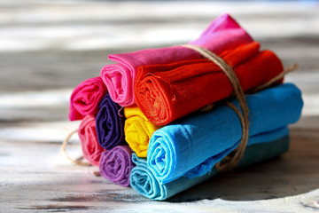 Rolls of multicolored clothes bound by a piece of rope