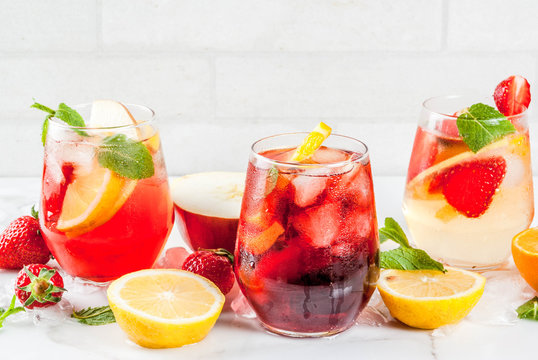 Cold white, pink and red sangria cocktails with fresh fruits, berries and mint.