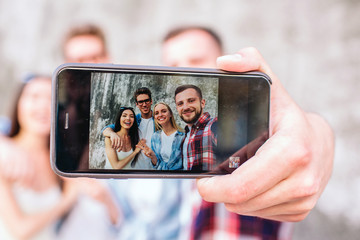 A picture of nice company. Guy is holding phone in hands nd taking selfie of him and his friends. They are smiling and posing on camera.