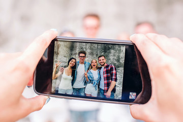 A picture of human's hands holding phone. This human is taking picture of four happy people. They are standing on grey background, posing and smiling.