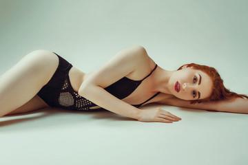 Model shoot in studio. Skinny girl with red long hair posing in the black knitted swimsuit bikini lying on the floor