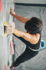 From above of anonymous sportive woman with hands in chalk training in gym and climbing wall with artificial boulders