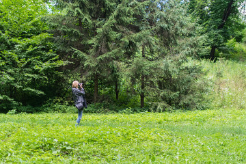 Woman photographer taking photo in a green forest in the summer.