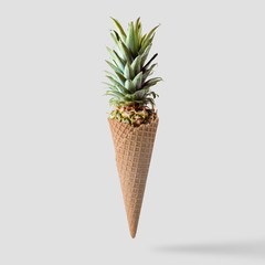 Ice cream cone with pineapple leaves on bright background. Minimal fruit and candy concept.