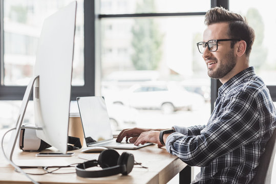 smiling young man in eyeglasses using laptop and desktop computer at workplace