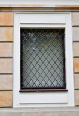 White window with metal grid for security on yellow facade of building close up view.