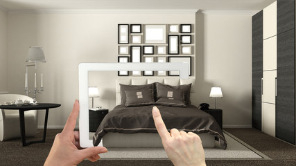 Augmented reality concept. Hand holding tablet with AR application used to simulate furniture and interior design products in real home, hotel bedroom