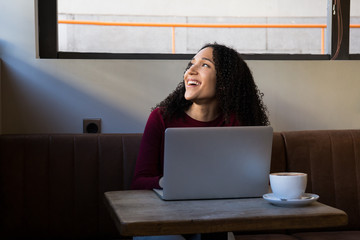 Charming African-American woman at table in cafeteria with laptop and cup of coffee looking away and laughing, Madrid