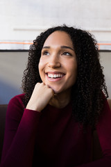 Beautiful young African-American curly woman in casual outfit leaning on hand at table and laughing