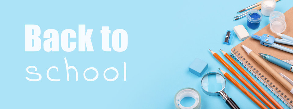 School stationary on blue background with inscription Back to school. Notebook, pens, pencils and other tools. Banner for website.