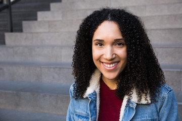 Young casual ethnic woman with curly hair wearing denim jacket and smiling happily at camera sitting on steps