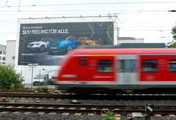 A train drives past an Opel advertisement poster in Ruesselsheim