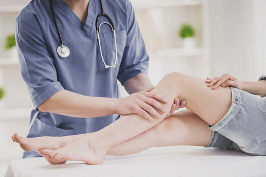 Close up. Doctor Comfforting Leg of Sitting Woman.